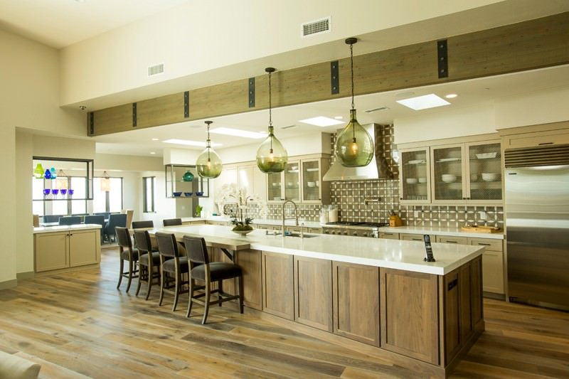 This is a wide kitchen with a long kitchen island that has wooden cabinets and drawers that match the hardwood flooring. This has a white countertop that contrasts the black cushions of the wooden chairs paired with the breakfast bar. This is topped with three glass pendant lights and a large wooden beam.
