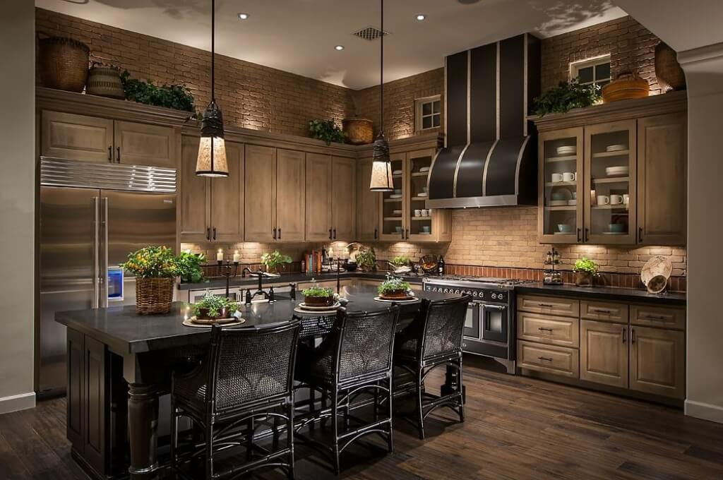 This impressive Southwestern-style kitchen has textured brick walls that complements the wooden shaker cabinets and drawers of the L-shaped peninsula. This is contrasted by the black stove and its hood that matches with the kitchen island.