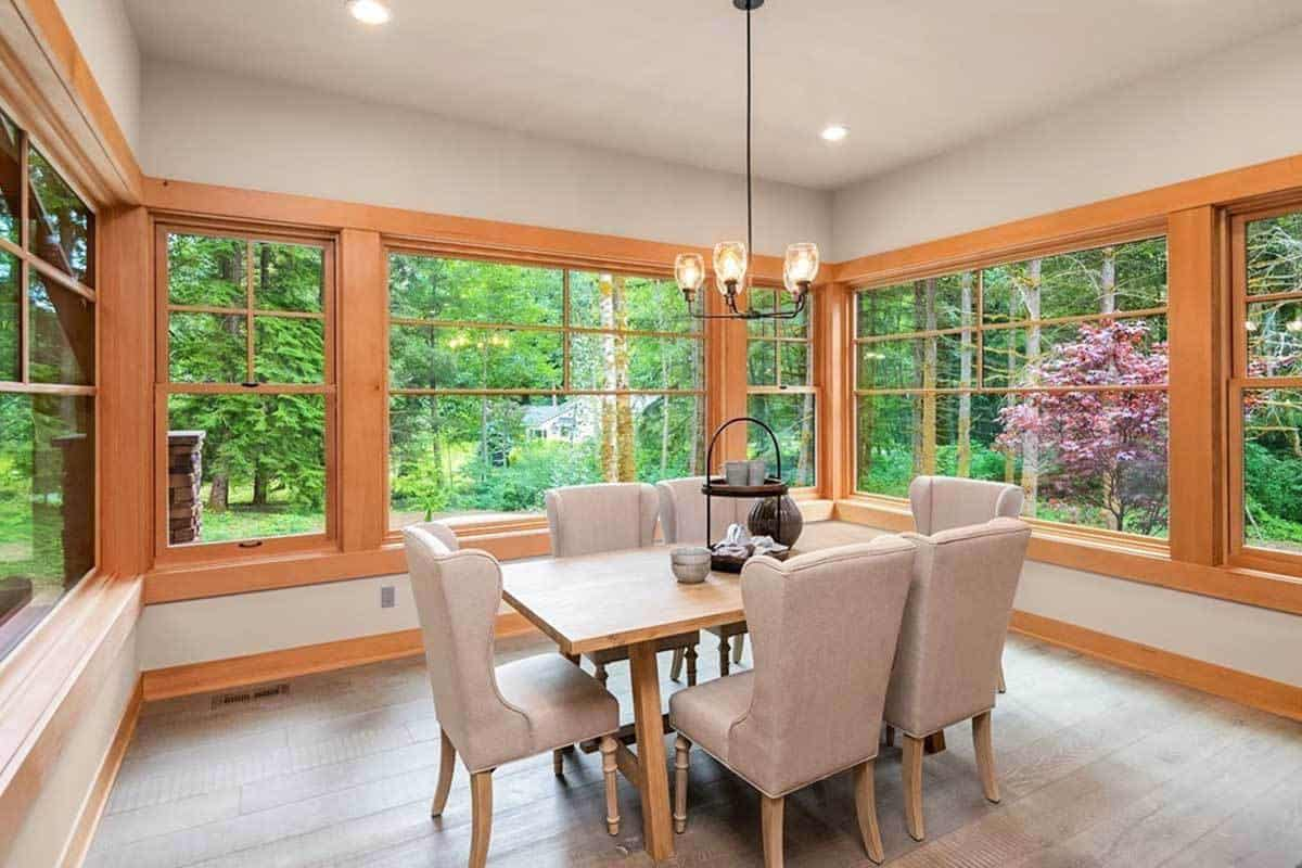 This lovely dining room is complemented by the lush green scenery afforded by the surrounding glass windows with wooden frames that match the dining table that us surrounded by cushioned dining chairs and topped with a simple chandelier.