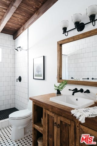 The wooden ceiling with exposed beams of this Spanish bathroom matches with the built-in cabinet of the sink and the frame of the wall-mounted mirror above it. The rustic dark faucet pairs well with the detail of the wall-mounted lamp and the bathroom tiles. The brick-style finish of the white wall tiles caps off the aesthetic.