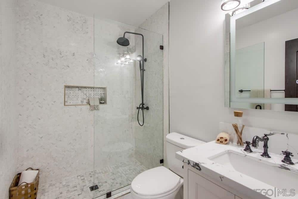 The rustic faucet and showerhead of this Spanish bathroom stand out amidst the mixture of white and light gray hues. wall-mounted modern lights and mirror seem to blend into the white sink and white walls that match the white toilet. The shower area is given wall and floor tiles with patches of light grey randomly mixed into the patterns.