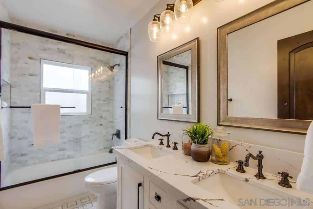 The long marble countertop accommodates two sink areas each with its own wall-mounted lights above the mirror. The rustic brass faucets harmonize with the frames of the mirrors and lights. A shower area with a bathtub is separated from the rest from the Spanish bathroom with a glass sliding door that is illuminated by a square window.
