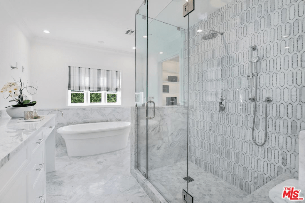 The bathroom floor tiles harmonize well with the patterned wall tiles of the shower area, marble of the wall and countertop of the sink making the bathtub stand out. The cabinet drawers share the stark whiteness of the tub, ceiling and the upper half of the walls which are further brightened by the pin lights and french window above the bathtub.