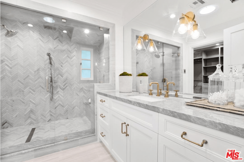 Against the whites and grays of this Spanish bathroom, the brass faucet, wall-mounted lamps, cabinet, and drawer handles stand out. An immense wall-mounted mirror dominates the wall above the grayish countertop of the sink and the pair of lamps are mounted on it. The grayish hues of the countertop are mirrored on the tiles of the shower room that extends from the walls to the floor.