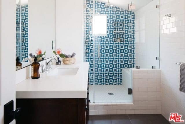The eye-catching patterns of the wall tiles in the shower area dominates this white Spanish bathroom with a shed ceiling. The glass door and wall-mounted mirror complement the white tiles while the dark wooden cabinet of the faucet blends with the dark-tiled floor.