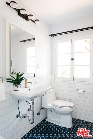 The deep sea green floor tiles of this Spanish bathroom gives it an eclectic taste while the geometric angles accentuate the modernism of the wall-mounted lamps above the mirror. The brass faucet, white walls, and tiles bring it back to its traditional roots.