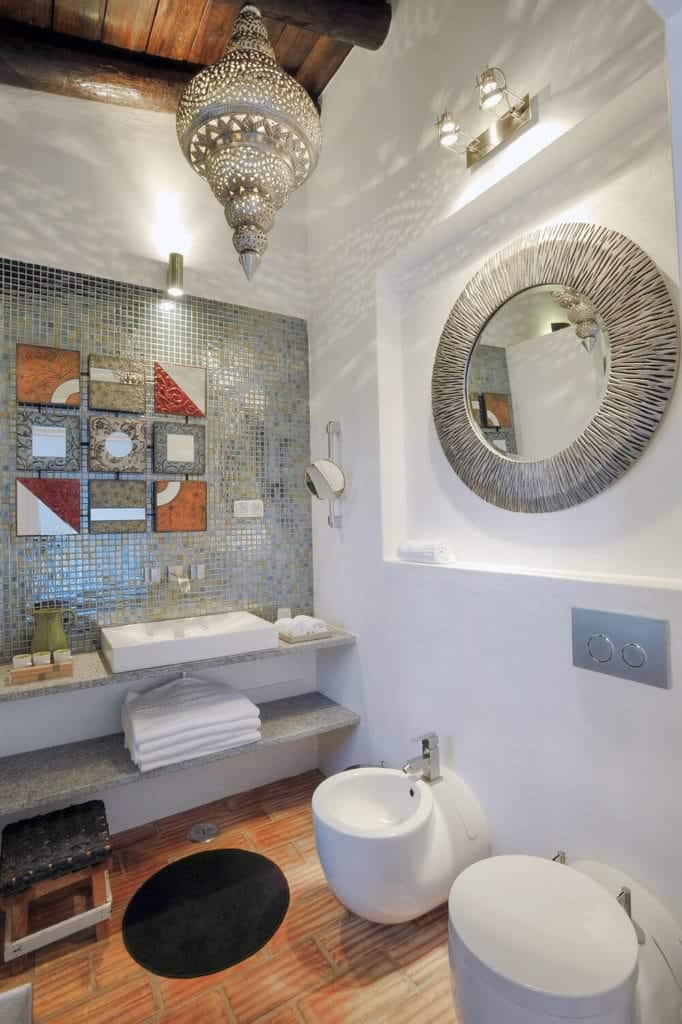 This eclectic Spanish bathroom is a symphony of details and patterns that starts with the white walls, sink, and toilet as its background. A peculiar seashell-like lighting is hanging from a wooden ceiling with exposed log beams. The wall-mounted mirror above the toilet has the same silver hue of the lighting and is complemented by the colorful tiled patterns above the sink that serves as a centerpiece art.