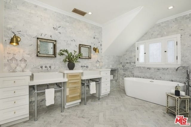 A gorgeous free-standing bathtub is placed below the white French windows. The light gray patterned tiles of the floor match with the walls and serve to accentuate the stark white cabinets flanking the two white sinks. The metallic wall-mounted brass lamps and mirrors give this Spanish bathroom a touch of modernism.