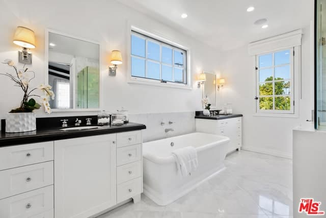 This white Spanish bathroom has two vanity areas with its own wall-mounted mirror, faucet, and black counter-top sink. Between them lays a sleek and white bathtub with a horizontal French window above it. The bathroom is illuminated by pin lights from the white ceiling and warm light from the wall-mounted lamps flanking the mirrors.