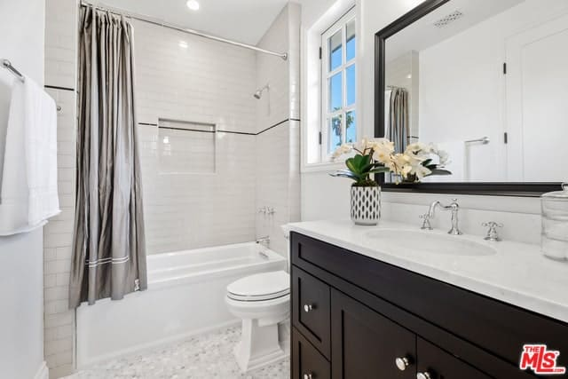 The grayish silver shower curtain matches the faucets and shower and serves as a contrast to the white tub and toilet with a white French window above it. The combination of gray and white are also mirrored on the floor tiles. The dark brown of the cabinet sink and borders of the wall-mounted mirror gives the room depth.