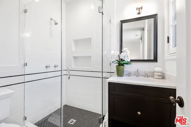A small and modern Spanish bathroom with an elegant cabinet sink with a white countertop. It matches well with the wall-mounted mirror with a small lamp above it and a French window beside it. The monotony of the pure white walls is broken by two peculiar black lines that accentuate the patterned black tiles of the floor.