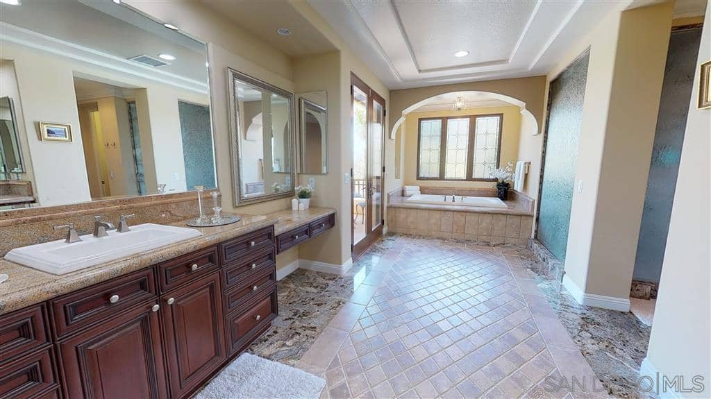 This is a spacious bathroom with an elegantly tiled floor and a white tray ceiling. The beige walls complement the bathtub area's tiles and frame it beautifully with an arched entryway illuminated by three French windows. Dark wooden cabinets add a touch of sophistication and tradition to this luxurious Spanish bathroom.