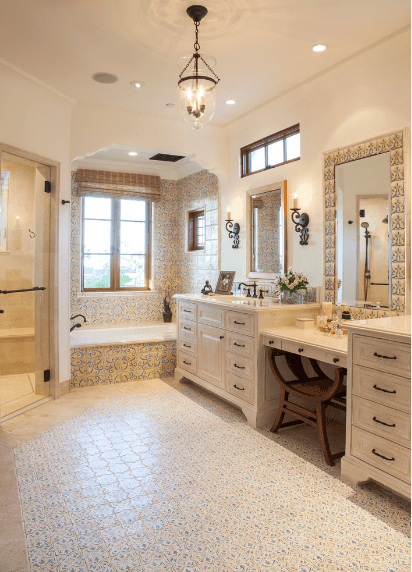 The unique patterned tiles of the floor and walls are carried over to the frame of the vanity mirror. This is also inlaid into the walls of the bathtub alcove by a pair of French windows. Another smaller window is placed above the mirror and wall-mounted lamps of the sink area. The lamps pair well with the unique pendant lighting hanging from the white ceiling.