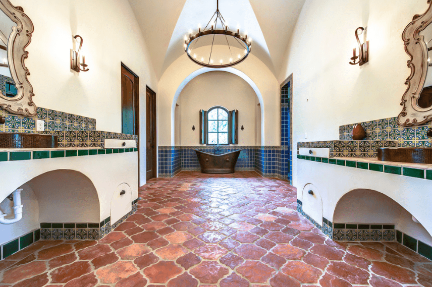 The dark brown bathtub by the arched French window is a perfect reflection of the wall-mounted lamps and the modern chandelier hanging from a groin-vaulted ceiling. The blue tiles of the walls and patterned tiles of the two vanity areas complement the terracotta floor quite nicely, completing the overall aesthetic of this Spanish-style bathroom.