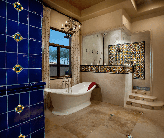 The colorful patterned tiles adorning the walls of the shower area contradicts the marble of the Spanish bathroom and this patterned tile is peppered across the marble floor. A touch of tradition is provided by the hanging chandelier above the bathtub and a curtained window beside it.