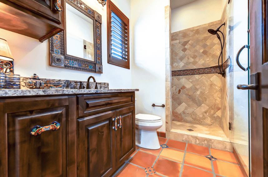 Sporadic additions of colorful patterns are scattered across this Spanish bathroom, giving it a touch of southwestern vibe. It is seen on the framework of the wall-mounted mirror, accessories on the countertop of the sink, handles of the built-in cabinets and even on the terracotta floor. It also mid-lines the marble of the shower area walls.