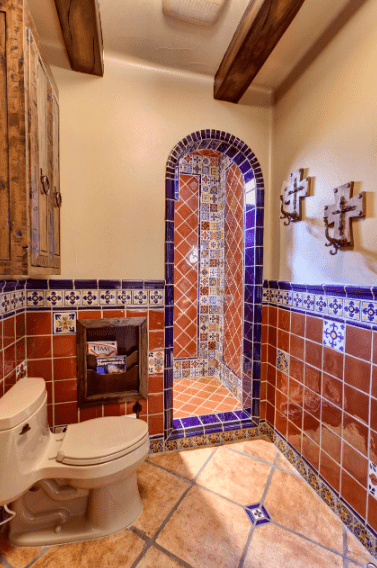 The brown and blue tiles of the walls along with the patterned tiles form a distinctive look that is a perfect match to the exposed wooden ceiling beams and wall-mounted cabinet. The wooden magazine rack by the beige toilet gives this Spanish bathroom a sense of cozy warmth.