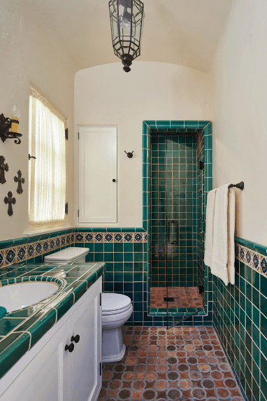 The terracotta floor of this Spanish bathroom represents the earth to the forest colors of the teal walls. The white upper walls serve as the sky background that extends to the cove ceiling where a lantern-type semi-flush mount lighting hangs.