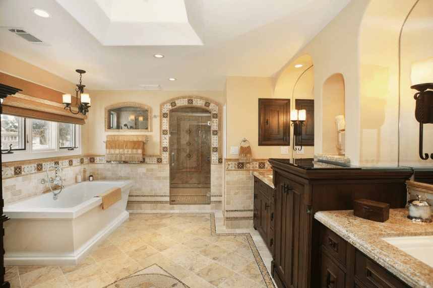 The marble floor matches the marble countertop of the two vanity areas with built-in cabinets made of dark wooden material. The mirrors are alcoved into the beige walls and flanked by a pair of wall-mounted iron lamps that provide warm light to this Spanish style bathroom.