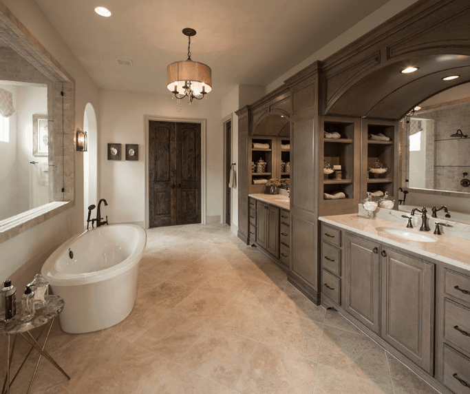 The wooden muted brown hues of the built-in vanity alcoves serve as the centerpiece to this elegant Spanish bathroom. A wall with a glass opening separates the shower area from the free-standing bathtub that goes well with the marble floors and white walls. Capping off the aesthetic is a small chandelier that hangs in the middle of the room.
