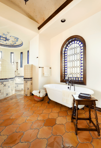 This airy Spanish bathroom's beauty is amplified by the arched window with stained glass patterns by the white bathtub. Its frame also matches the dark wooden stool and the terracotta floor that contrasts the white walls and high ceiling.