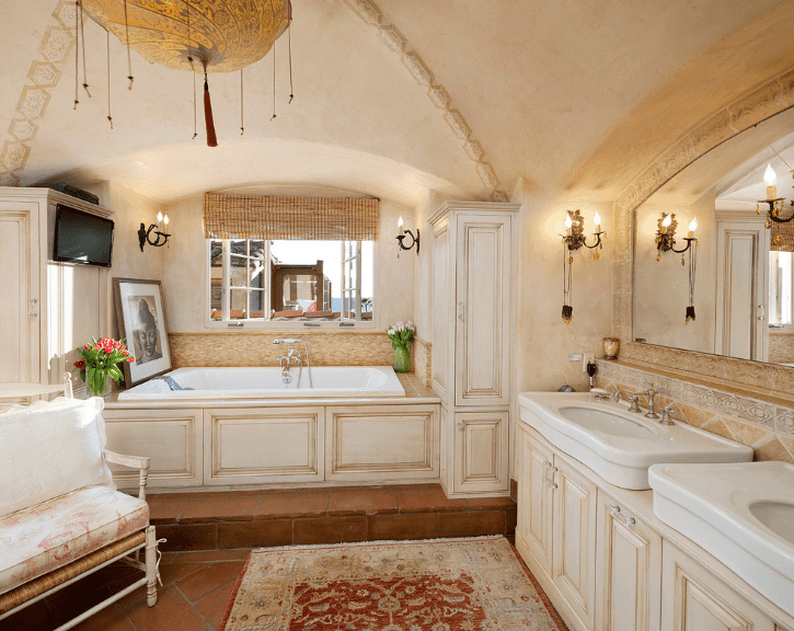 The groin vaulted ceiling of this Spanish bathroom is the perfect staging point for the peculiar patterned lighting that is reflected in the patterned rug on the terracotta floor. The magnificent arched mirror is built into the wall with an elaborate border that pairs perfectly with the wall-mounted lamps on either side. The two sinks and the design of its wooden cabinets are carried over into the bathtub and its wooden alcove housing.