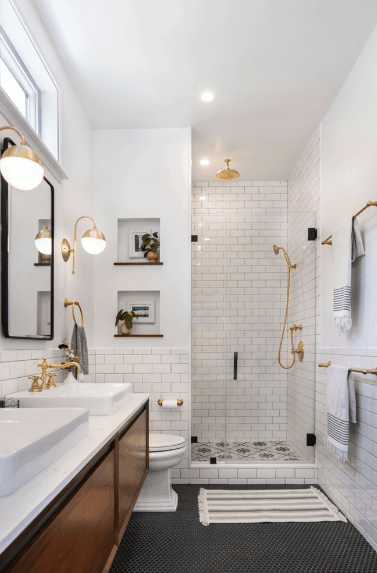 Those brilliant golden faucets and shower set are paired perfectly with the bathroom fixtures and the two wall-mounted lamps. It is a nice contrast to the dark floor tiles and white-tiled walls. A pair of square wall alcoves that are decorated with framed photos and potted plants bring warmness to the bathroom.