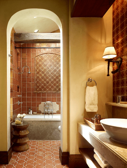 Warm yellow lights bring an intimate comfort to this Spanish bathroom. This is further enhanced by the beige walls paired with brown tiles on the walls and patterned floor. The modern oval sink is a contrast to the traditional wooden stool and exposed beam hanging over the built-in bathtub.