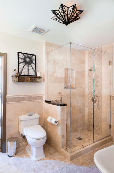 Above the toilet is a mounted shelf with a black and white framed photo. This photo greatly resembles the pattern of the angular semi-flush mount lighting which illuminates this Spanish bathroom with a warm yellow glow. This warm yellow light plays well on the marble walls and the beige tiles of the floor.