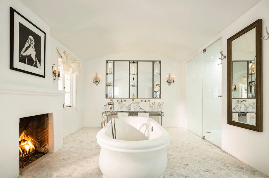 The white fireplace is the perfect partner to the free-standing bathtub in the middle of the white-tiled floor. The marble countertop of the sinks is partnered to a huge square wall-mounted mirror with glass shelves and two lamps mounted on their side. The framed artwork and the mirror mounted across it serve to amplify the homey feel to this Spanish bathroom.