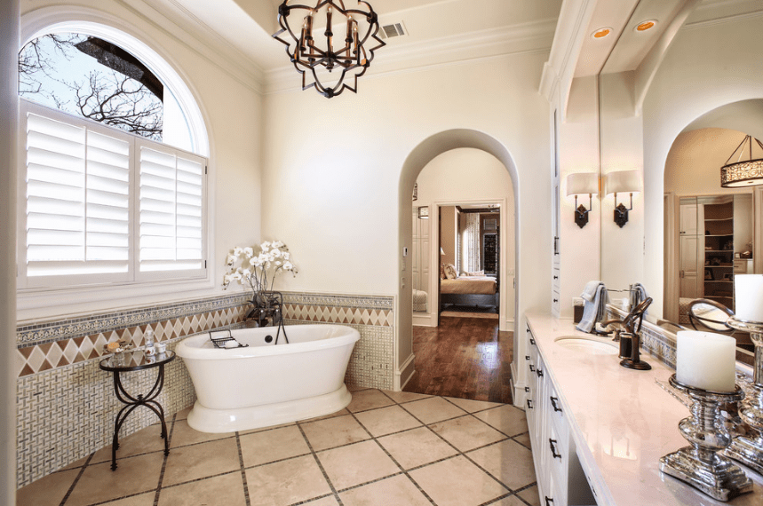 An intimate and comfortable tub is given a corner by the white shuttered windows. Across from it, a is a long vanity area with a white countertop and built-in alcove mirror. The dark iron fixtures of the bathroom match well with the modern chandelier hanging from a tray ceiling.