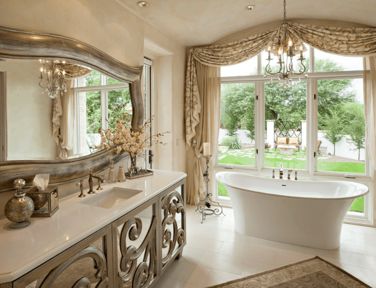 Elegance and luxury are the two themes of this traditional Spanish bathroom. The huge wall-mounted mirror has a silvery border that matches the patterns of the sink cabinet beneath it and the area rug by the white bathtub. This bathtub stands beside a floor-to-ceiling glass window that opens to the garden outside.