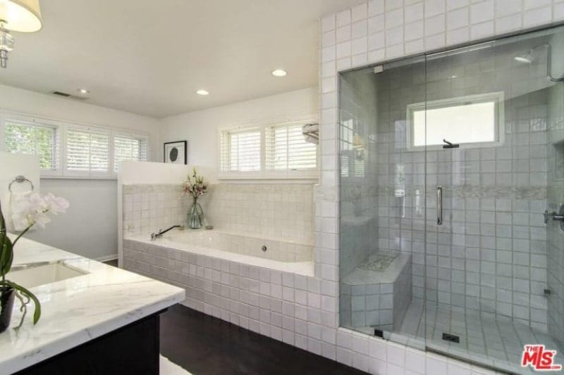 The simple and traditional white square tiles of the bathtub and shower area are a good contrast to the dark hue of the floor and sink cabinet. These are all illuminated by ample light coming from the windows and pin lights on the white ceiling.