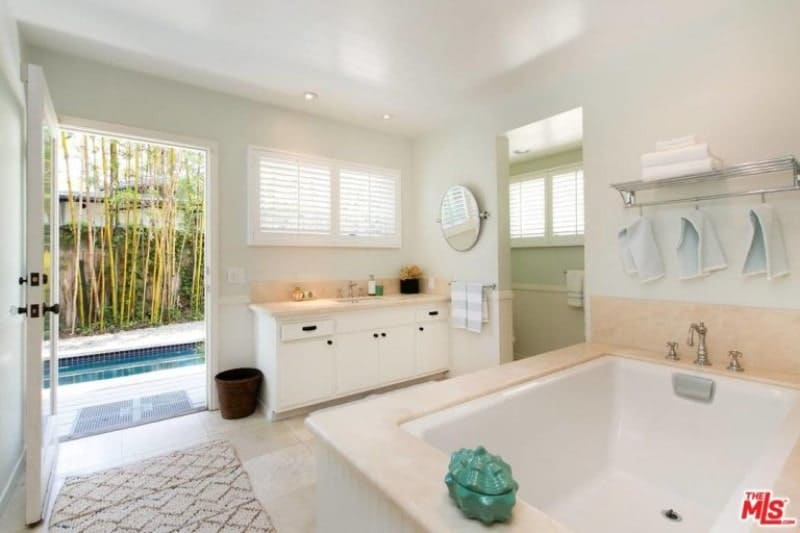 The accent of the beige countertop of the sink is duplicated on the beautiful bathtub making it appear like a larger version of the sink. gorgeous shuttered windows and a door leading to the pool outside gives this simple white Spanish bathroom a sense of warmth and comfort.