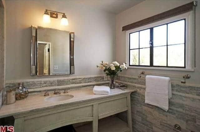 Simple yet elegant lamps are mounted above the mirror flanked with silver accents. The marble countertop of the sink is an elegant addition and contrast to the wall tiles with marble patterns. The natural light coming from the square windows accentuates the subtle details of this Spanish bathroom.