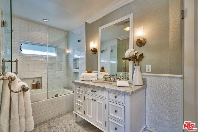 The warm yellow light from the wall-mounted lams on either side of the mirror illuminates this Spanish bathroom. Benefitting from this yellow light are the gray details of the tiled-floor and gray walls as well as the marble countertop of the sink. The glass door and white tiles of the bathtub and shower area separate it from the rest of the bathroom.
