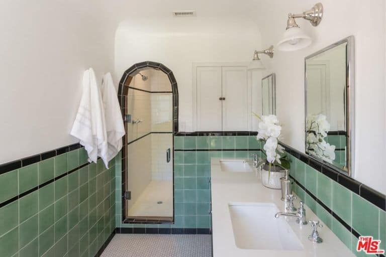 The stand-out detail of this Spanish bathroom is the light green wall tiles with a black outline that curves with the arched doorway of the shower area. The long white countertop of the pair of sinks contrasts the colorful tiles and it mirrors the white upper half of the walls and white ceiling. Silver faucets that match the wall-mounted lamps and mirrors balance the two contrasts.