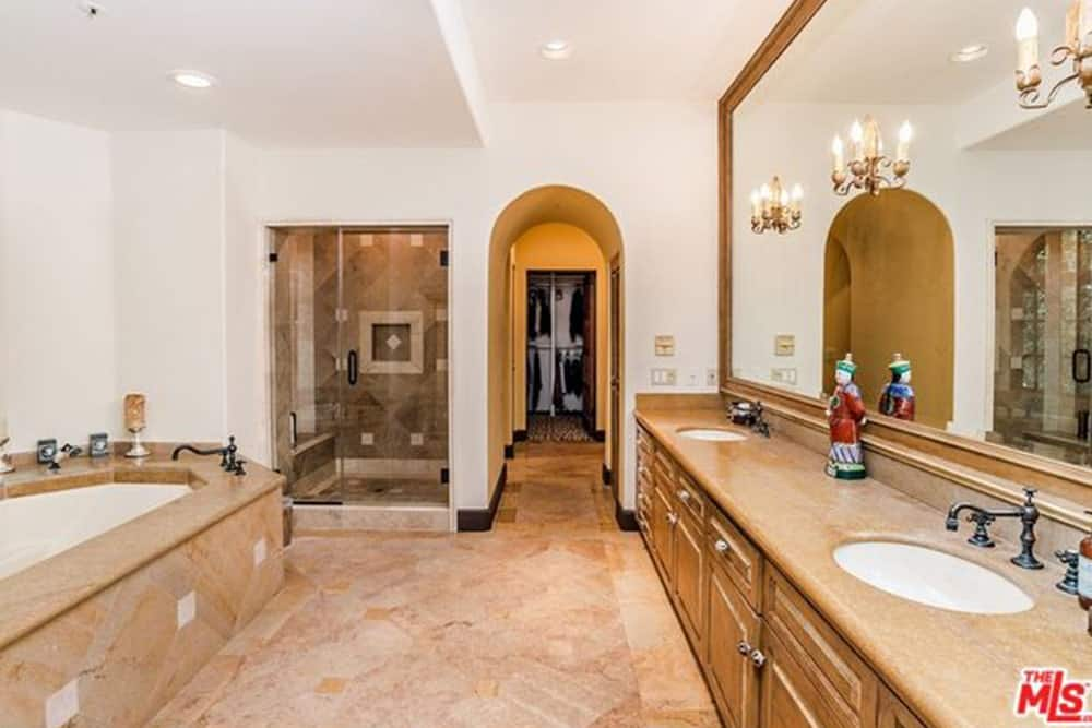 A massive wall-mounted mirror dominates this room. It has a wooden frame that matches well with the countertop and cabinet of the sink and three lamps mounted on it. The beige marble of the floor blends into the bathtub and provides a good contrast to the white walls and matching rustic dark faucets.