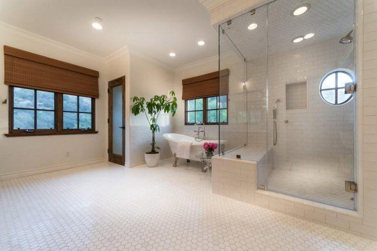 This is a spacious Spanish bathroom that exudes comfort. It has a white tiled floor that extends to the walls of the shower area which is separated from the rest of the room by glass. A comfortable free-standing bathtub is given a nook at the corner by the French window. The potted plant beside it caps off the aesthetic.