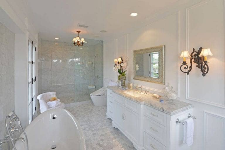 This bathroom has an elegant miniaturized chandelier hanging from the white ceiling that pairs well with the wall-mounted lamps on either side of the vanity area. The white cabinet of the sink has built-in drawers that blend into the whitewalls that have an elegant finish. The contrast between the white walls and grayish tiled floors extend to the shower area.