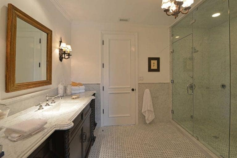 A beautiful floor-to-ceiling glass wall forms a boundary between the shower area and the rest of the Spanish-style bathroom. The small chandelier hanging from the ceiling matches with the wall-mounted lamps while the cabinet of the sink matches with the artwork mounted by the white door.