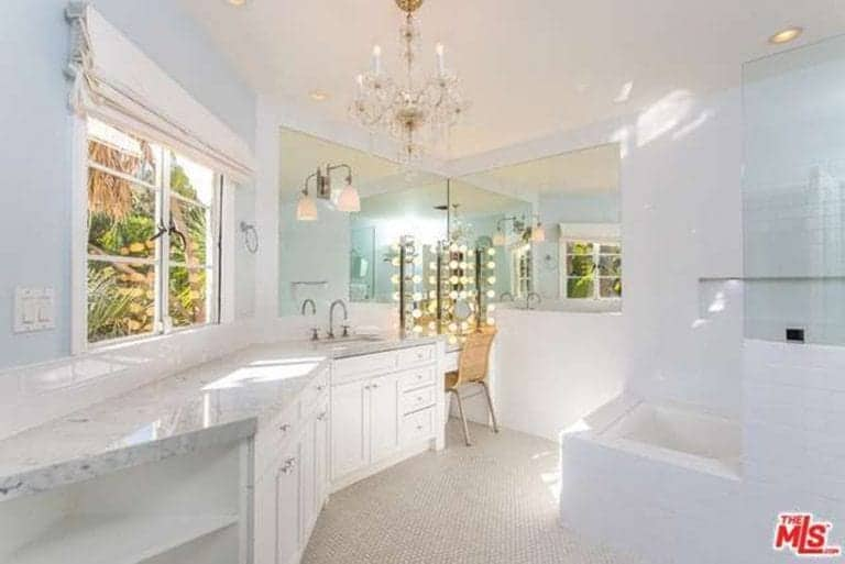 The light hues of the walls and tiles are enhanced by the natural light coming from the French windows. This is supplemented by the majestic gold and crystal chandelier hanging from the white ceiling. The marble countertop of the sink follows the irregular shape of this Spanish bathroom leading to a sophisticated vanity area with its own ample lighting.