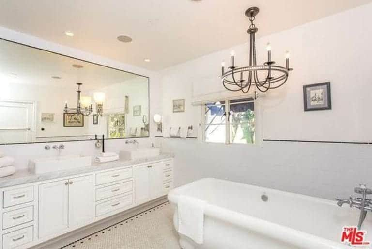 The modern chandelier hanging over the white bathtub provides a lovely contradiction to the whiteness of the walls. The long wall-mounted mirror above the sinks amplifies the chandelier's lights and supplemented by the pin lights on the corners of the ceiling.