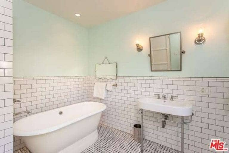 A simple and comfortable Spanish-style bathroom that has light hues on the upper half of the walls and ceiling. The wall tiles are arranged in a brick wall patterned and given dark outlines to accentuate the pattern. The tiled floor has a patterned design that complements the walls.