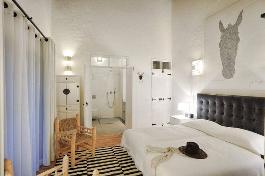 The Spanish room features a horse wall art mounted above a dark headboard of the bed opposite to two wooden rustic chairs. They are atop an area rug with black and white stripe designs that gives a good contrast to the whiteness of the bed and walls.