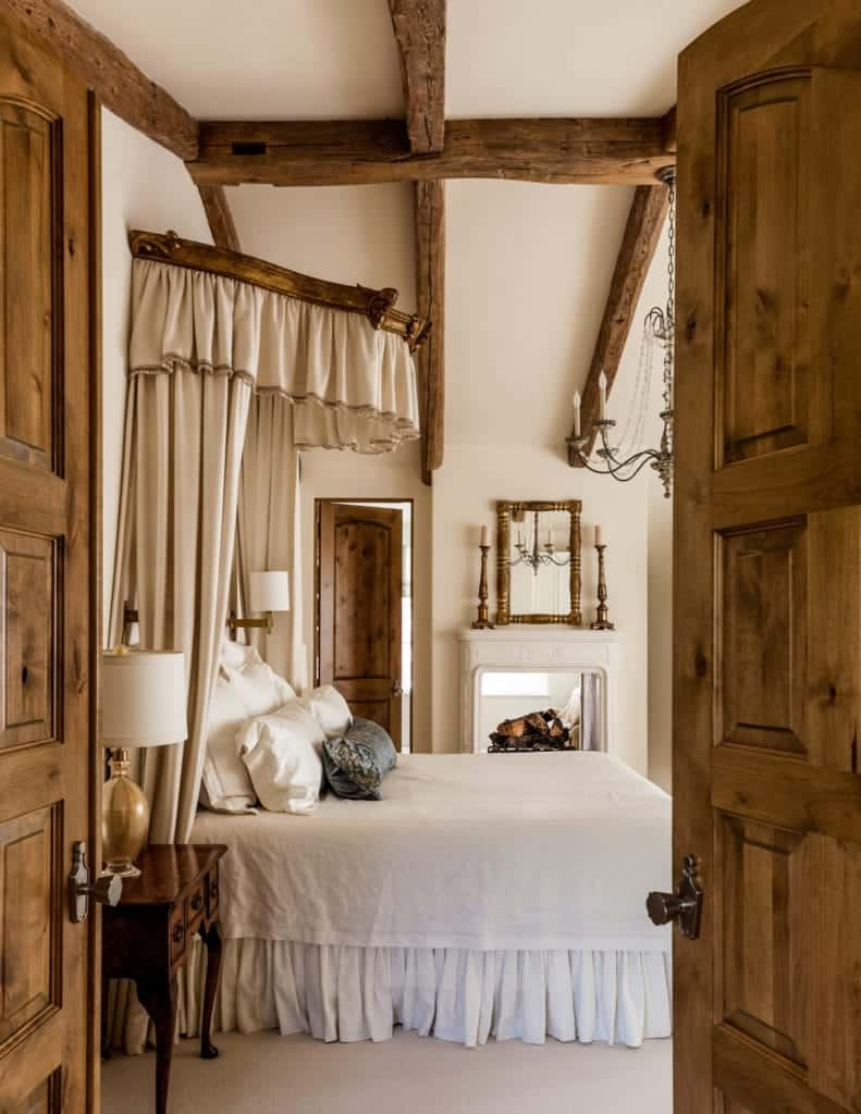 A very cozy room that is dominated with the wooden details of the exposed beams of the vaulted ceiling, doors and side table. It has a feel of a cottage bedroom, that is further enhanced by the fireplace at the side of the bed. However, the brass details of the chandelier, candle-stand, and mirror give it an elegant boost.
