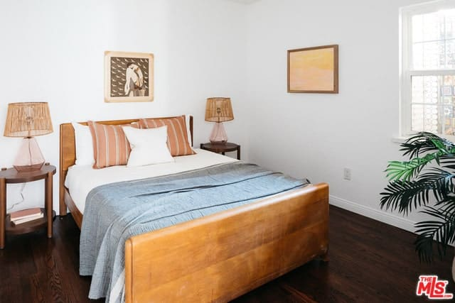 The earthy tones of this white-walled room give it a homey warmth. Particularly, the pair of table lamps beside the bed with the rattan details give the Spanish bedroom a unique character. This is further emphasized by the dark wood floors and the wall-mounted artwork.