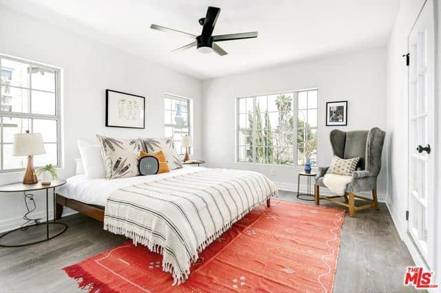 An airy primary bedroom complemented by its oversized windows. The natural light coming into the bedroom goes well with the white walls and white bed. It also provides a good light source for the reading area at the corner of the room that has a cozy gray chair. The cherry on top is the brilliant addition of the patterned colorful rug.