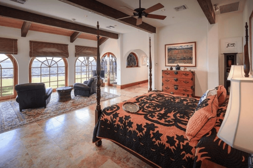 This Spanish-style bedroom is made for sunsets. The viewing deck and reading area across the bed is dominated by three large dome windows that offer a great view. Colorful marble floors blend well with the bedspread and redwood drawer at the side of the bed. On the sidelines, the dark wood details of the four-poster bed and exposed ceiling beams serve to cap off the over-all elegance of the room.