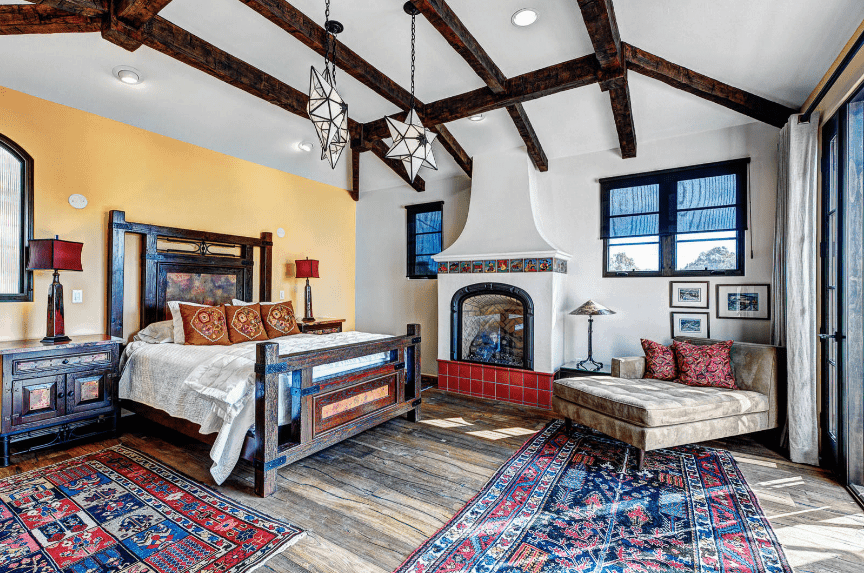 An airy and vibrant Spanish bedroom with patterned details on two area rugs, pillows and tile fittings above the fireplace. The dark wooden bed frame has the same finish and material as the exposed beams of the white ceiling. An addition of three teardrop star-shaped lighting gives it an air of eccentricity.
